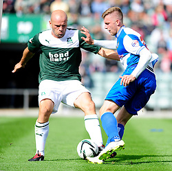 Bristol Rovers' Ryan Brunt is tackled by Plymouth Argyle's Guy Branston  - Photo mandatory by-line: Dougie Allward/JMP - Tel: Mobile: 07966 386802 07/09/2013 - SPORT - FOOTBALL -  Home Park - Plymouth - Plymouth Argyle V Bristol Rovers - Sky Bet League Two
