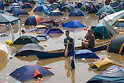 Scavengers in a Canadian canoe search the field of flooded tents at the very wet 2005 Glastonbury festival.