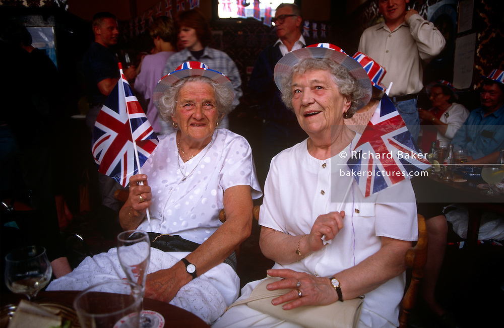 Elderly ladies wave union jack flags and enjoy an afternoon of nostalgia in their local east end pub in east London, remembering the 50th anniversary of VE (Victory in Europe) Day on 6th May 1995. In the week near the anniversary date of May 8, 1945, when the World War II Allies formally accepted the unconditional surrender of the armed forces of Germany and peace was announced to tumultuous crowds across European cities, the British still go out of their way to honour those sacrificed and the realisation that peace was once again achieved. Street parties now - as they did in 1945 - played a large part in the country's patriotic well-being.