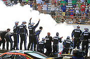 Driver Jimmie Johnson's crew celebrate on the wall as Johnson does a burnout marking his Brickyard 400 win. The Brickyard race was held at the Indianapolis Motor Speedway on Sunday, July 29 2012. Mike Fender / The Star