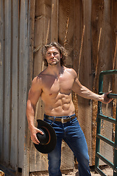 sexy muscular cowboy by a rustic barn