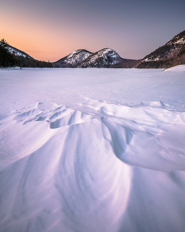 A snow drift from strong north wind seems to point directly at the Bubbles on Jordan Pond in Acadia National Park.