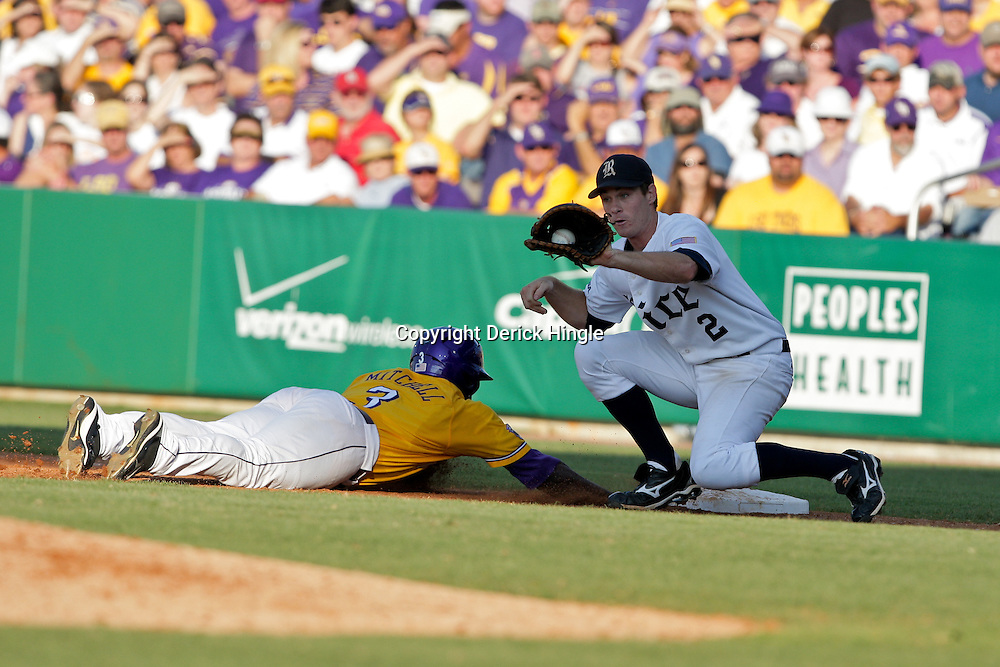 05 June 2009:  LSU base runner Jared Mitchell dives as Rice first baseman Jimmy Comerota catches the ball during game one of the NCAA baseball College World Series, Super Regional game between the Rice Owls and the LSU Tigers at Alex Box Stadium in Baton Rouge, Louisiana.