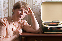Elderly woman sits listening to old fashioned record player
