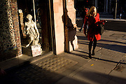 Woman returns for dropped item near small girl statue credited to the 19th century Florence-born artist Raffaello Romanelli. Part of a sequence of 4 images showing the woman in red dropping the Oyster card and subsequently bending down and picking it up.