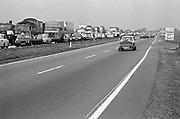 Oost Duitsland, DDR, Leipzig, 1-7-1990 File op de snelweg naar Berlijn. Er is een ongeluk gebeurd. De snelweg heeft geen vangrail in de middenberm. Een auto keert naar de andere kant. Op 1 juli 1990 werd de duitse monetaire eenwording effectief. De burgers van de ddr konden hun marken, ostmarken, inwisselen tegen de west-duitse mark, in winkels vond een grote operatie plaats om prijzen aan te passen en westerse producten in de schappen te leggen. weg,wegen,snelwegen,verkeerFoto: Flip Franssen/Hollandse Hoogte