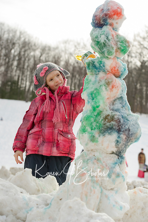 "Lorelai Shepherd decorates her snowman with a ""Picasso-like"" style during Laconia Parks and Recreation snow building activity on Thursday afternoon.  (Karen Bobotas/for the Laconia Daily Sun)"