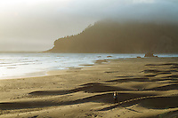 Image of woman walking on the beach in Southern Oregon.