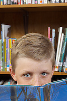 Boy peeking above book, close-up view