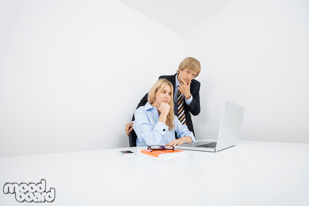 Businesspeople with hand on chin looking at laptop in office