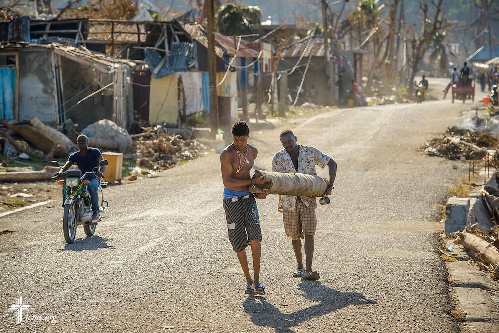 Men clear debris caused by Hurricane Matthew on Wednesday, Oct. 12, 2016, in Port-Salut, Haiti. LCMS Communications/Erik M. Lunsford