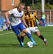 Chris Hussey is on the ball and guards it from Byron Moore  during the Sky Bet League 1 match between Bury and Port Vale at Gigg Lane, Bury, England on 19 September 2015. Photo by Mark Pollitt.