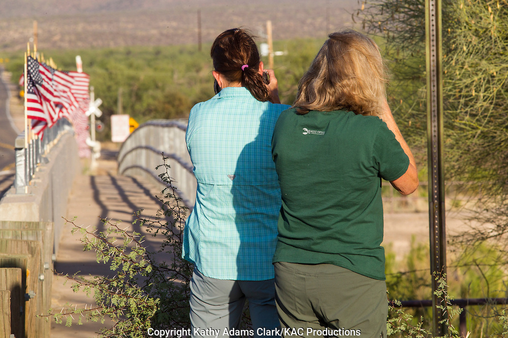 Karen McCormick and Jenny Shuffield photographing American flags on Elephant Head Road in southern Arizona.