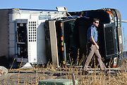 Colorado State Patrol trooper walks past a rolled over truck at the intersection of Colo. 66 and Weld County Road 1 on Wednesday, Feb. 11, 2015.<br /> (Matthew Jonas / Longmont Times-Call)