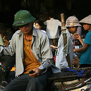 A man checks his mobile phone at Dong Xuan Market, the largest market in Hanoi, Vietnam.