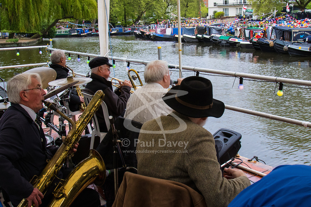 Little Venice, London, May 3rd 2015. After a dull, damp start to the day, hundreds of Londoners and narrowboat enthusiasts arrive at Paddington Basin at the juction of the Regents and the Grand Union Canals for the annual Inland Waterways Association's Canalway Cavalcade, celebrating the history and traditions of Britains vast network of canals and navigable rivers. PICTURED: Bob Dwyer's Bix and Pieces Jazz Band entertains the crowd from a floating bandstand.
