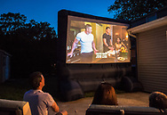 "Merrick, New York, USA. 11th June 2017.  At bottom left, CHRIS EDOM, ""American Grit"" TV contestant, 48, of Merrick, hosts backyard Viewing Party for Season 2 premiere. The Fox network reality television series show projected on large screen, with (L-R) JOHN CENA, and 2 of his Cadre members, JOHN BURKE and RIKI LONG. Edom was last contestant picked for a team that episode."