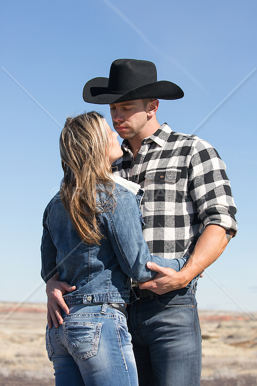 cowboy and girl outdoors embracing
