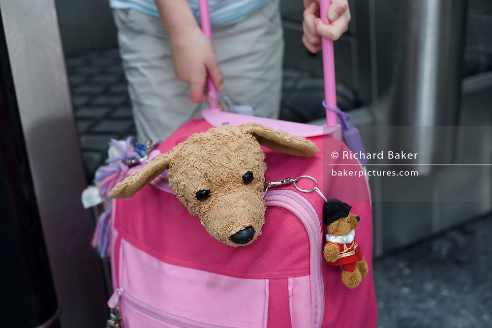 Childrens' toy dog and pink baggage in check-in areas at Heathrow Airport's Terminal 5.