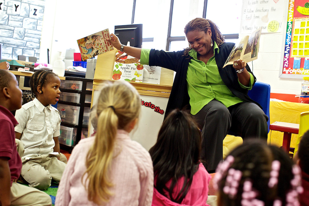 "Pre-kindergarten students at Calvin Rodwell Elementary School No. 256 in Baltimore, MD, including James Manley III, 4, listen to their teacher Erika Parker, right, as they read the book ""A Day at the Pumpkin Patch,"" a non-fiction children's book about visiting a farm. The book was part of a ""Common Core"" reading and learning unit, which aims to follow up non-fiction reading with learning in the field. The day after the children read the book about the farm, they visited Summers Farm in Frederick, MD."
