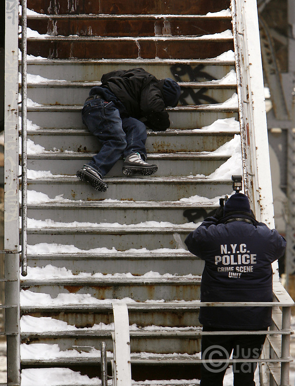 A member of the New York Police Department Crime Scene Unit photographs the body of a man who murdered on the Willis Avenue Bridge Monday 16 January 2006 in the Bronx, New York. The bridge, which was built in 1901 and runs between Manhattan and the Bronx, is being offered for sale by the City of New York for $1 (usd) because it is set to be replaced in 2007. Circumstances surrounding the murder were unknown.