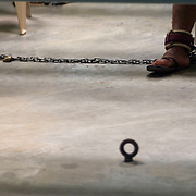 A detainees shackled foot seen below a desk where he is taking a class in Camp 6 at the Guantanamo Bay Detention Facility in Guantanamo Bay, Cuba. The detainees held in this facility were captured after the attacks on the United States on September 11, 2001. In 2009 US president Barack Obama ordered the closure of the facility, yet to date it still remains open. These Photos were reviewed by military officials before release.