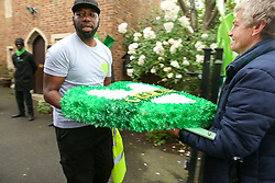 "© Licensed to London News Pictures. 14/06/2019. London, UK. Men carry a ""Grenfell"" wreath inside St Helen's Church  for the second anniversary of the Grenfell Tower fire service. On 14 June 2017, just before 1:00 am a fire broke out in the kitchen of the fourth floor flat at the 24-storey residential tower block in North Kensington, West London, which took the lives of 72 people. More than 70 others were injured and 223 people escaped. Photo credit: Dinendra Haria/LNP"