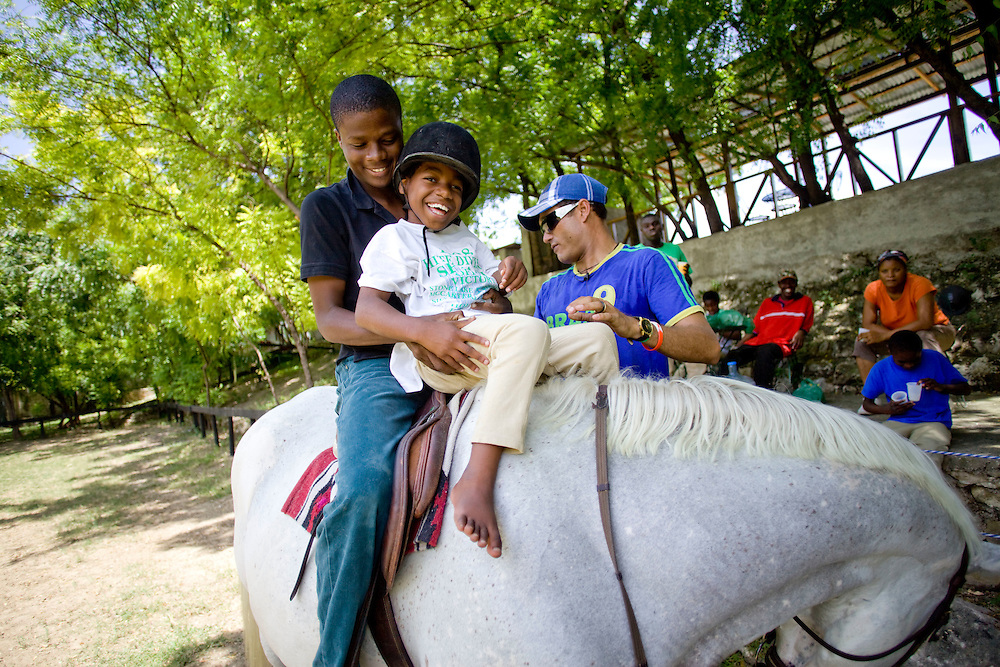 Equestrian Club employee Normandy Chery helps Josephine Michel, age 9,  (all the chilren's last names are Michel because that is the name of the orphanage director) rides a horse during an equestrian therapy session with Athletic Club Centre Equestre manager Paco Gonzales. For two years Gonzales has been doing equestrian therapy with young people with disabilities from the Wings of Hope orphanage in Fermathe. Gonzales, formally a professional horse jumper, was inspired to start doing equestrian therapy after an accident left him unable to walk for two years. Gonzales says the children have been transformed by the horse riding and some have become more emotionally stable. One of the children, Vivian Michel, has improved her ability to walk. All of the children have learned how to ride.