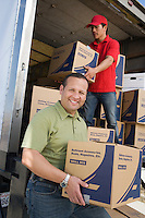 Portrait of man unloading with worker truck of cardboard boxes