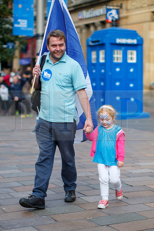 © Licensed to London News Pictures. 18/09/2014. Glasgow, UK. People walking in Glasgow city centre with Scottish Saltire flags whilst people of Scotland going to polling stations to vote on the Scottish independence referendum on Thursday, 18 September 2014. Photo credit : Tolga Akmen/LNP