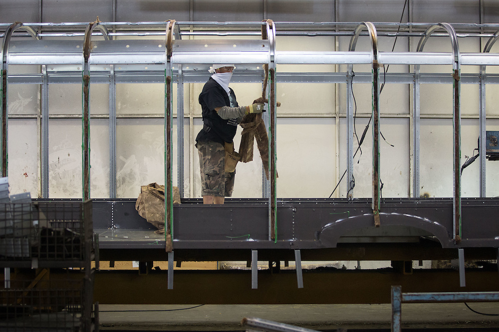 A factory worker installs installation on a school bus in Blue Bird's manufacturing plant on Tuesday, April 15, 2015 in Fort Valley, Ga. Photo by Kevin Liles for The New York Times