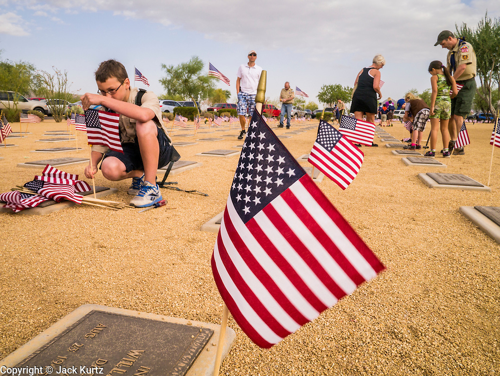 26 MAY 2012 - PHOENIX, AZ: People American flags on a veterans' grave at the National Memorial Cemetery in Phoenix, AZ, Saturday. Hundreds of Boy and Girl Scouts along with the Young Marines, a Scout like organization, place American flags on veterans' graves in the National Memorial Cemetery in Phoenix every year on the Saturday before Memorial Day.       PHOTO BY JACK KURTZ