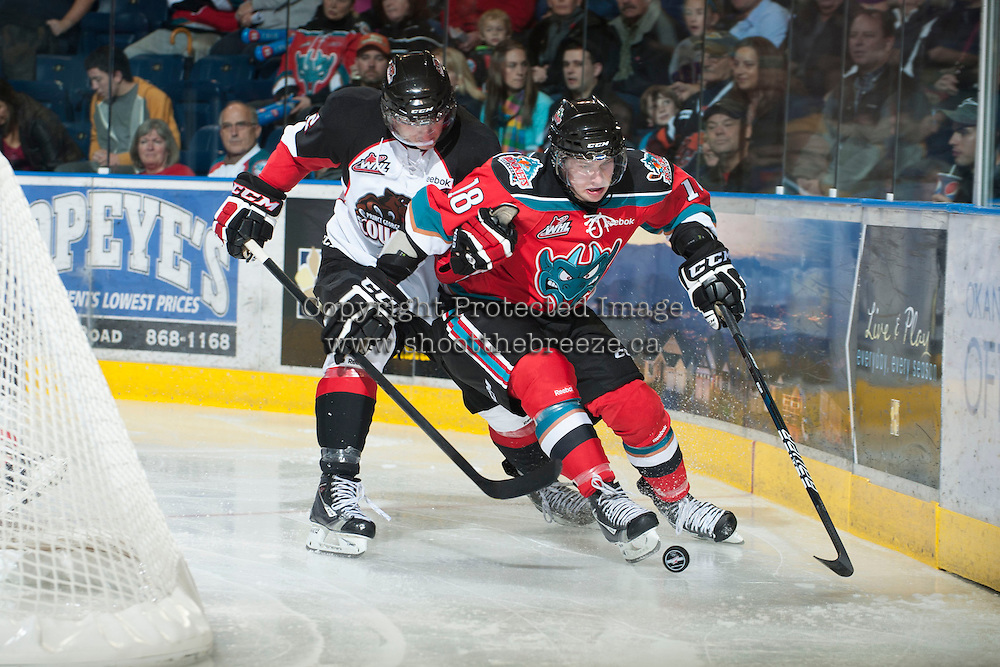 KELOWNA, CANADA - NOVEMBER 3:  Cody Fowlie #18 of the Kelowna Rockets skates on the ice with the puck while checked by a player of the Prince George Cougars at the Kelowna Rockets on November 3, 2012 at Prospera Place in Kelowna, British Columbia, Canada (Photo by Marissa Baecker/Shoot the Breeze) *** Local Caption ***