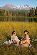 USA, Oregon, Lane  County, Willamette National Forest,Scott Lake,couple with dog tanning at lake<br /> <br /> MR  0514, 0515