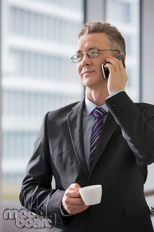 Businessman with coffee cup using cell phone in office