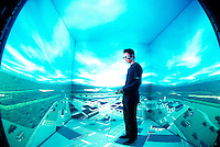 Photo ©Tom Wagner photograph of a the room where the avatar is filmed/monitored for projection into the virtual meeting environment of the five-screen projection display system (floor, ceiling and three walls, a virtual meeting space). The person's avatar can be seen to move and talk in real time at any size chosen by the viewer in this display space. <br /> Research done by Prof. Hirose of Tokyo University. Photographed at Tokyo at Tokyo University at the Intelligent Modeling Laboratory.<br /> The same technology at work here can be used for presenting 3-D images over a supehighway of a Network. (The virtual theater display currently in Tokyo is set up by the same professor)<br /> Shown are Kunihiro Nishimura, a PhD studebnt working with Prof Hirose as well as one of the students working on the project, <br /> www.tomwagnerphoto.com