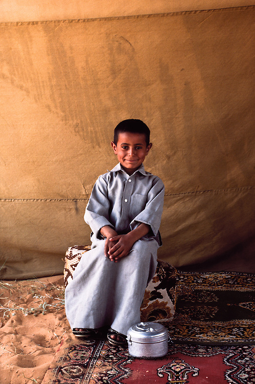 Ali, son of Nasser son of Mohammed Al Amrah.  Portrait with date container in tent encampment in Dahana Sands, Saudi Arabia