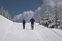 A couple of crosscountry skiers stride up the final approach to the Copper Creek Hut of the Mount Tahoma Trails Hut-to-Hut crosscountry ski and snowshoe trail system in the Washington state Cascade Mountain Range near Mount Rainier. USA