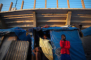 A woman strings a curtain over the doorway of a small store selling food items at a tent camp in the parking lot of Sylvio Cator soccer stadium in downtown Port-au-Prince, Haiti, April 8, 2011.  At the time, camp residents were being asked to leave so that the stadium grounds could be fully used for upcoming events.