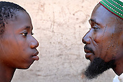Benin, Natitingou November 26, 2006 - Young boy and his father with the same facial scars . It represents the Prince of Djougou, smal city in the center of Benin Scarification is used as a form of initiation into adulthood, beauty and a sign of a village, tribe, and clan.