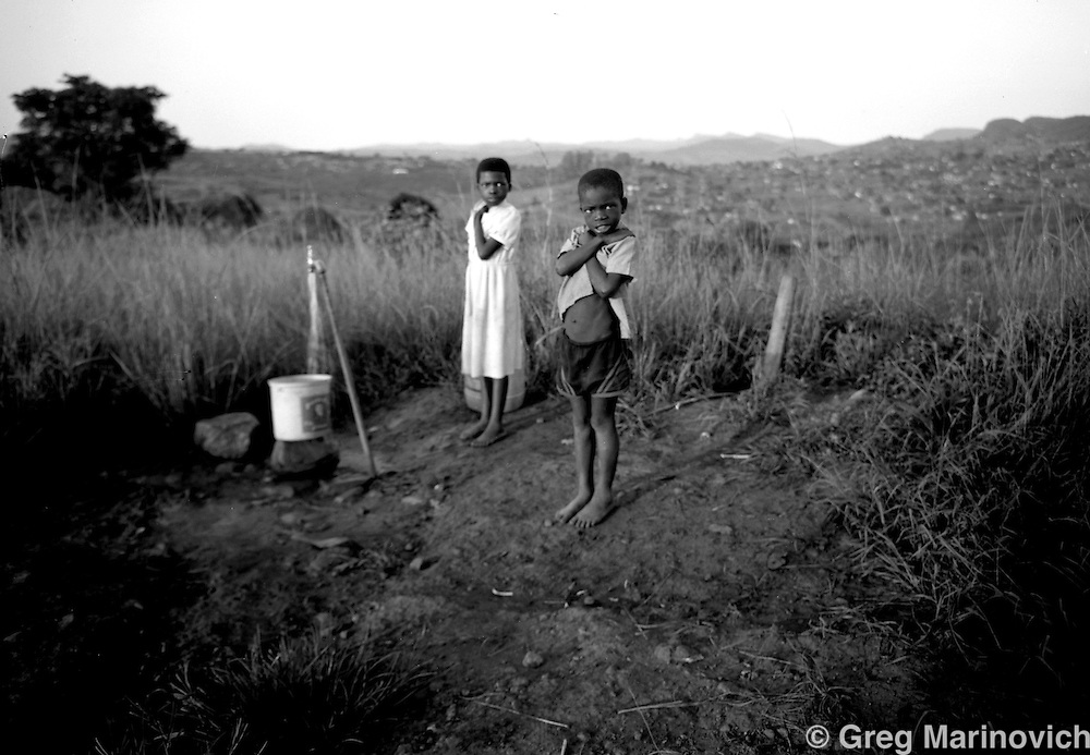 IPMG0091 South Africa, Gazankulu homeland,.Nov 1989: .Children collect water for laundry from a communal standpipe in Gazankulu homeland, South Africa. 1989. Access to water is still one of Africa's most pressing needs, ten years after apartheid was dismantled..Photograph by Greg Marinovich/South Photographs