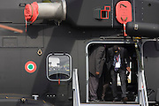 Visitors view a Finmeccanica helicopter exhibited at the Farnborough Air Show, England. Climbing into the aircraft through a low door, the visitors inspect its features. Finmeccanica S.p.A. is the leading industrial group in the high technology sector in Italy and one of the main global players in aerospace, defence and security. It operates in seven sectors: aeronautics, helicopters, space, electronics, defence systems, transportation and construction. The company has offices in over 100 countries. It is partially owned by the Italian government, which holds about 30% of Finmeccanica's shares.