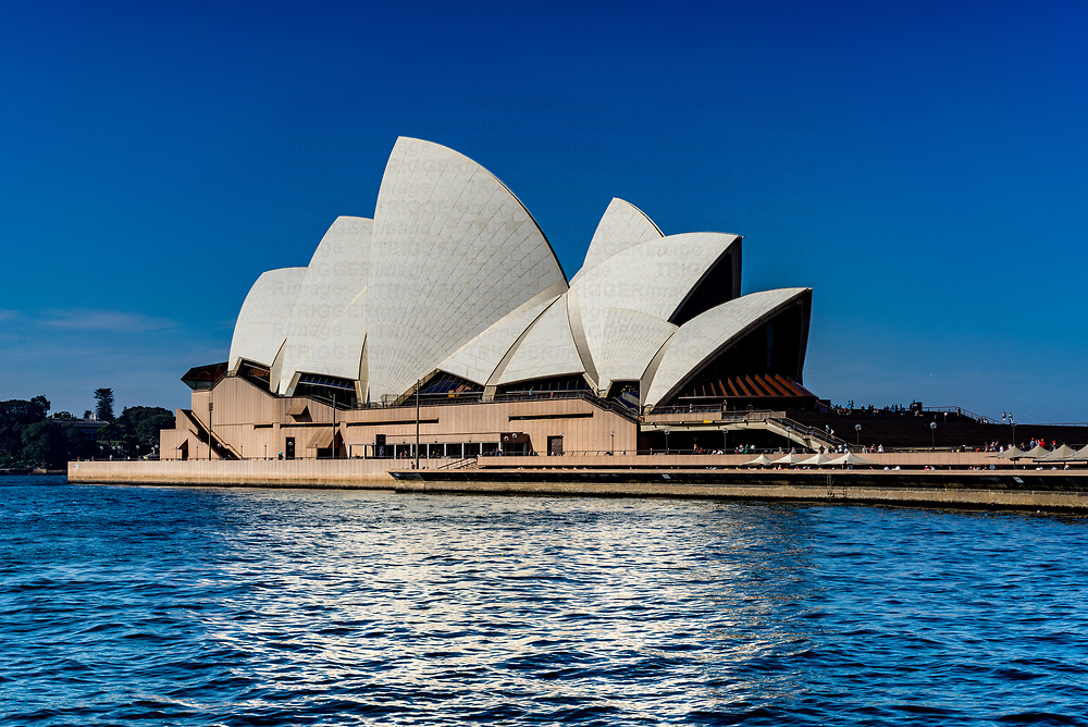 View of Sydney Opera House from the water. The Sydney Opera House is a multi-venue performing arts centre in Sydney, New South Wales, Australia. It is one of the 20th century's most famous and distinctive buildings. Designed by Danish architect Jørn Utzon, the building was formally opened on 20 October 1973. The building and its surrounds occupy the whole of Bennelong Point on Sydney Harbour, between Sydney Cove and Farm Cove, adjacent to the Sydney central business district and the Royal Botanic Gardens, and close by the Sydney Harbour Bridge. On 28 June 2007, the Sydney Opera House became a UNESCO World Heritage Site.