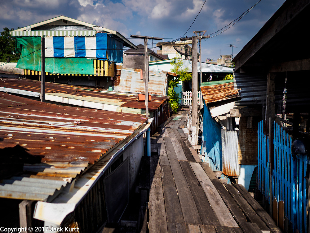 """20 JUNE 2017 - BANGKOK, THAILAND: Homes on stilts in a community along the Chao Phraya River south of Krung Thon Bridge. This is one of the first parts of the riverbank that is scheduled to be redeveloped. The communities along the river don't know what's going to happen when the redevelopment starts. The Chao Phraya promenade is development project of parks, walkways and recreational areas on the Chao Phraya River between Pin Klao and Phra Nang Klao Bridges. The 14 kilometer long promenade will cost approximately 14 billion Baht (407 million US Dollars). The project involves the forced eviction of more than 200 communities of people who live along the river, a dozen riverfront  temples, several schools, and privately-owned piers on both sides of the Chao Phraya River. Construction is scheduled on the project is scheduled to start in early 2016. There has been very little public input on the planned redevelopment. The Thai government is also cracking down on homes built over the river, such homes are said to be in violation of the """"Navigation in Thai Waters Act."""" Owners face fines and the possibility that their homes will be torn down.              PHOTO BY JACK KURTZ"""