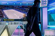 Genève, février 2018. Sandy Jeannin, consultant pour la rts Il commente un match de hockey des JO et donne des explications de séquences de jeux pendant la pause sur le plateau des sports. Ici Massimo Lorenzi, chef des sports, passe après avoir donné quelques ordres. © Olivier Vogelsang