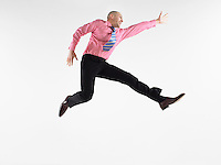 Businessman jumping in studio side view