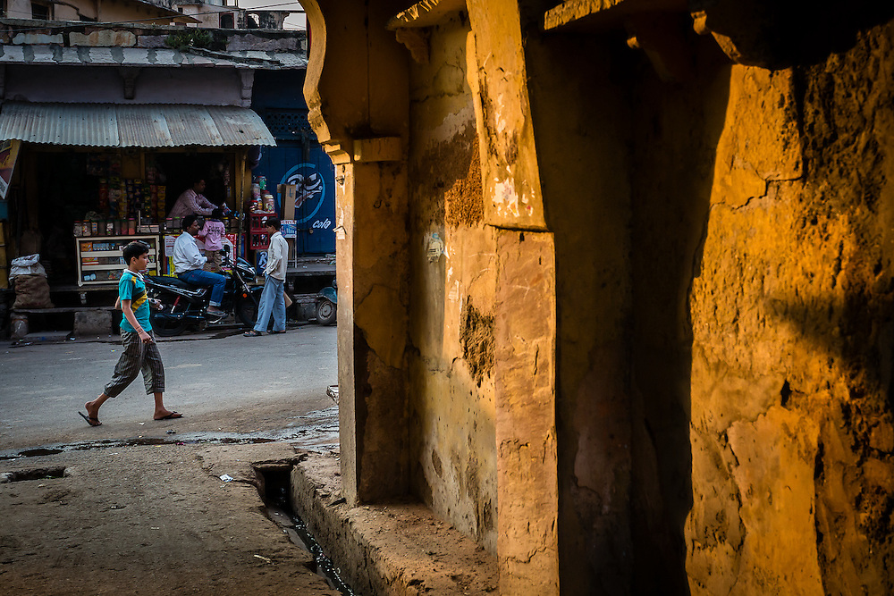 A kid walks on a street, near a yellow tunnel lit by the late afternoon light.