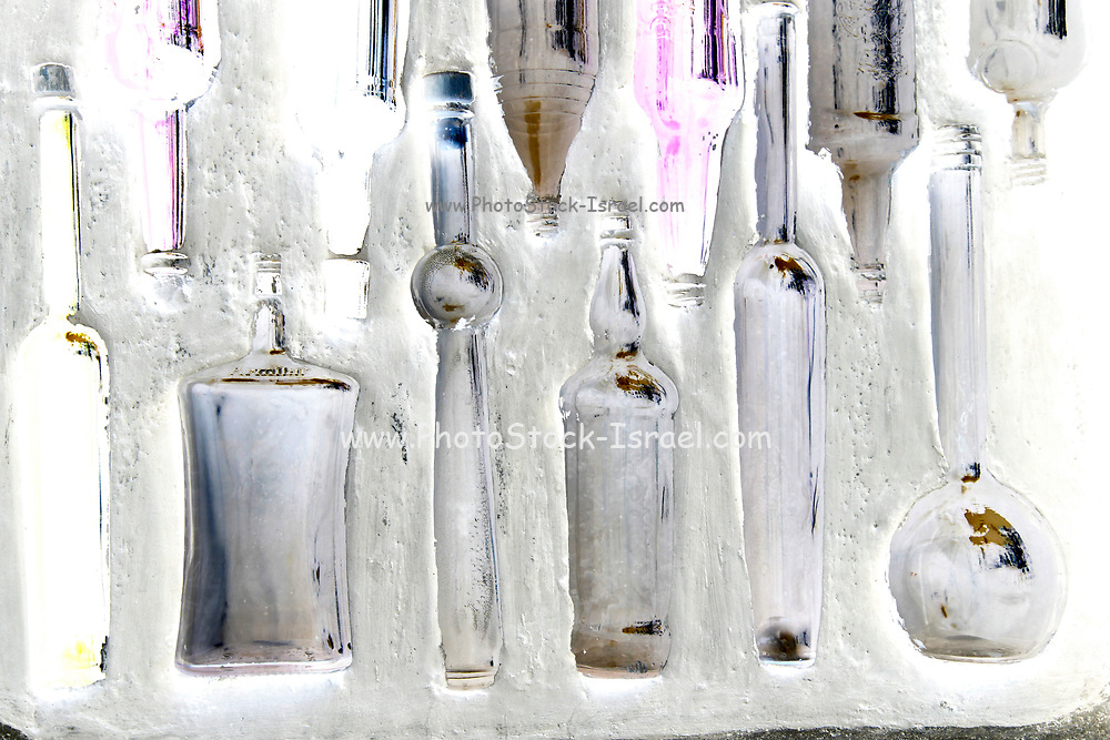Bottles in a wall - glass bottles embedded in a white washed wall