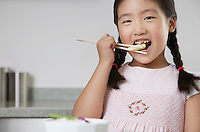 Young Girl with pigtails Eating Baby Corn with chopsticks