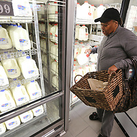 Jennifer Young, of Guntown, gets a gallon of milk as she shops during the grand opening of the new ALDI store during in Tupelo on Wednesday morning.